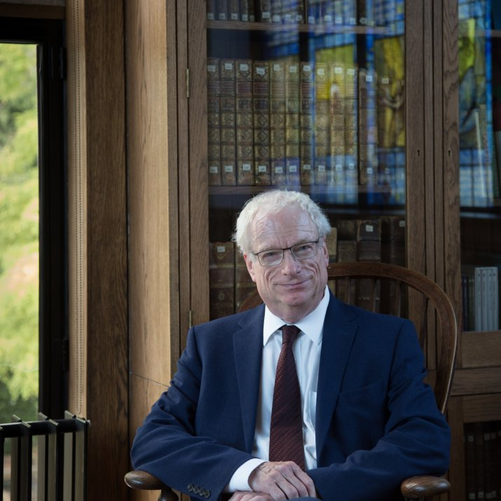 Photograph of Lord Chris Smith sitting in a chair in front of a bookcase. To the left of the photo is a window through which greenery can be seen .