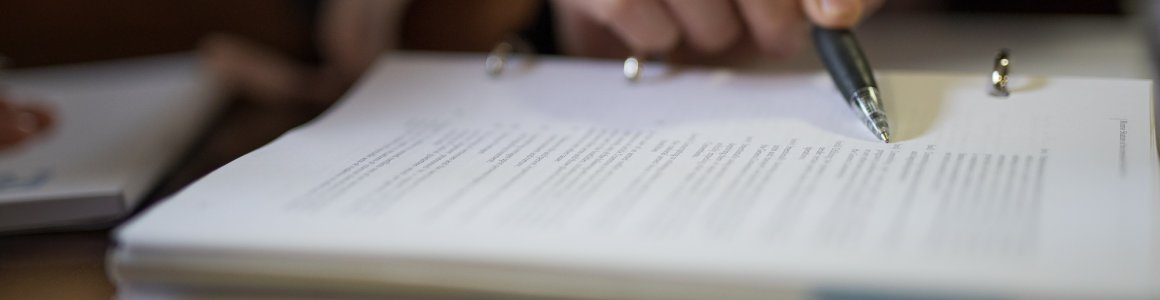 Image of pen pointing to a line on a document
