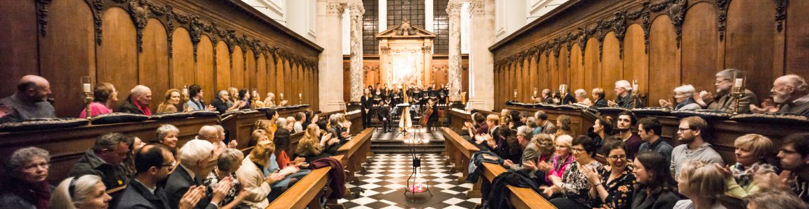 Image of The Pembroke chapel filled with a clapping audience applauding the choir
